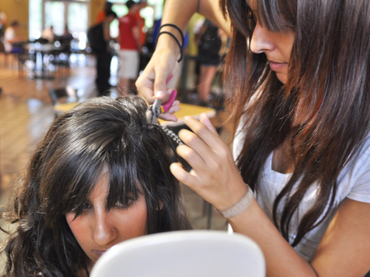Raquel Farinas secures one of her pieces into third-year hospitality major Aleen Touma's hair.