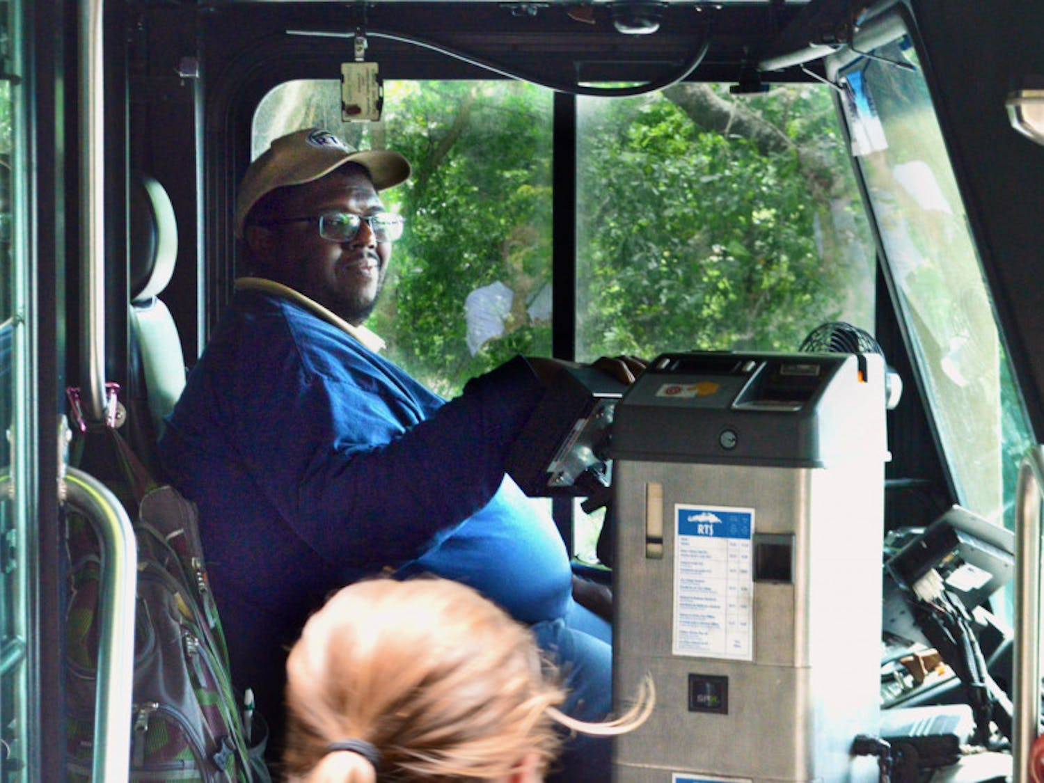 "Desmond Grimes, 38, welcomes students onto the 117 Bus at the Reitz Union. Grimes' route, ""Park-N-Ride 2,"" circulates through 34th Street back to the Reitz Union."