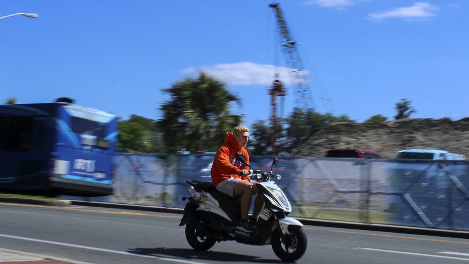 A person wearing a UF sweatshirt rides past a construction site on Museum Road across from the Reitz Union on Friday, March 19, 2021. (Photo by Chasity Maynard)