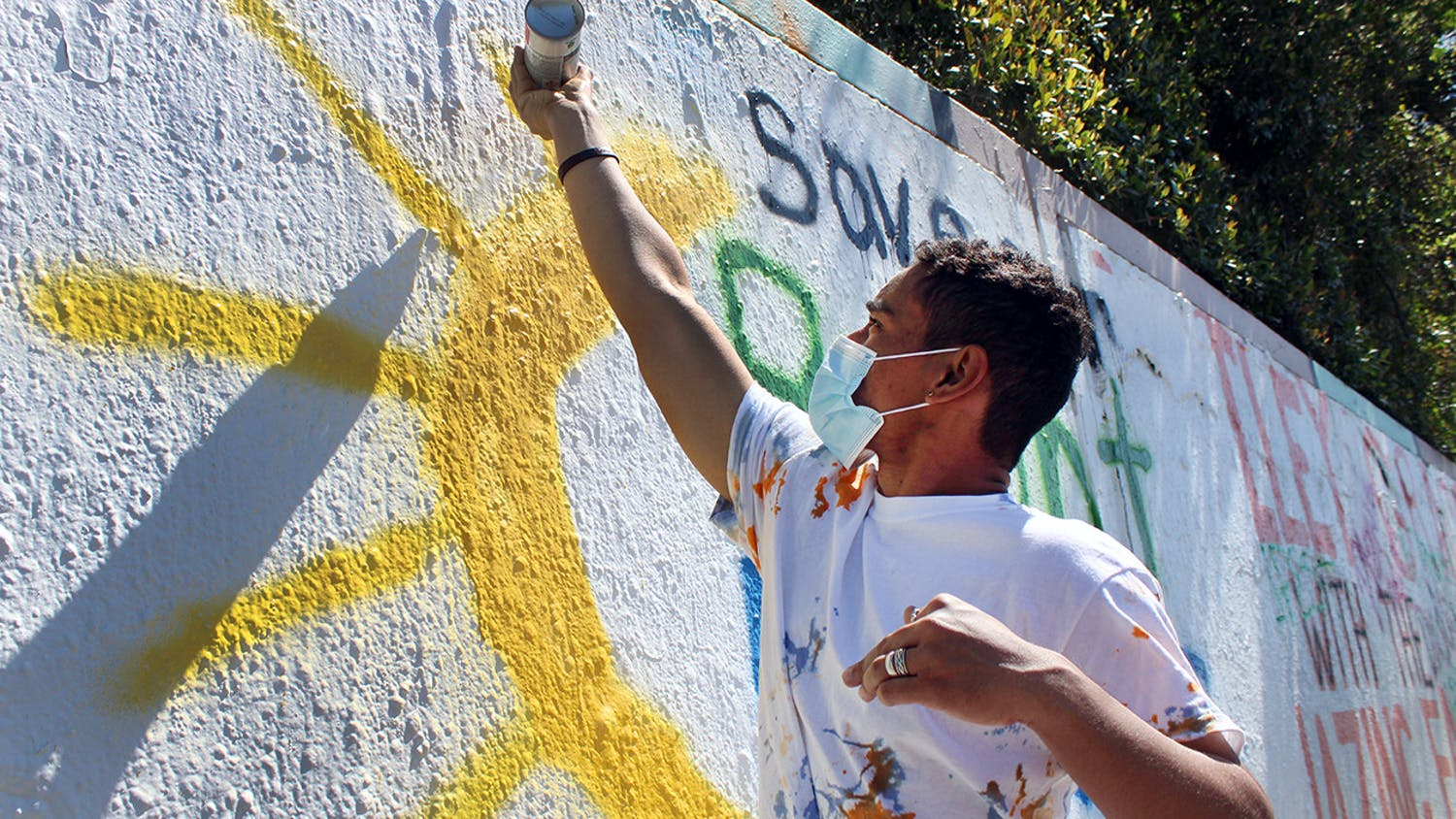"Oscar Santiago, 18, a political science freshman, finishes spray painting a sun on a mural that reads ""Save our Bright Futures"" on Sunday, March 7, 2021. The mural was painted in response to Senate Bill 86, which would limit some students' access to state funding, including the Bright Futures scholarship."