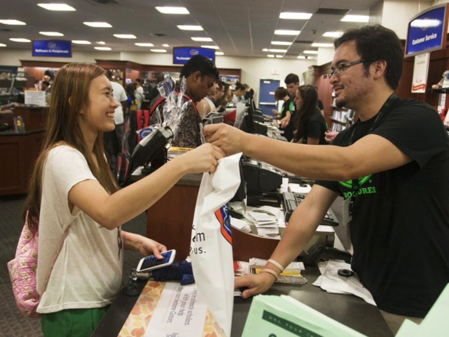 Freshman Truc Nguyen, an 18-year-old nutrition major, purchases books for her first semester from bookstore associate David Martinez, 25, Tuesday afternoon