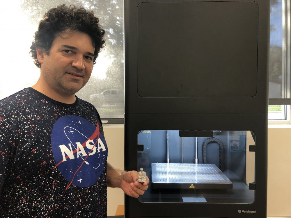 <p><span>Juan Griego stands next to the 3D metal printer with a model he printed of race car driver</span> <span>Dale Earnhardt</span><span>, one of the first pieces made by the new printer. The replica is based off a miniature he used for an art project. Kelly Hayes / Alligator Staff</span></p>