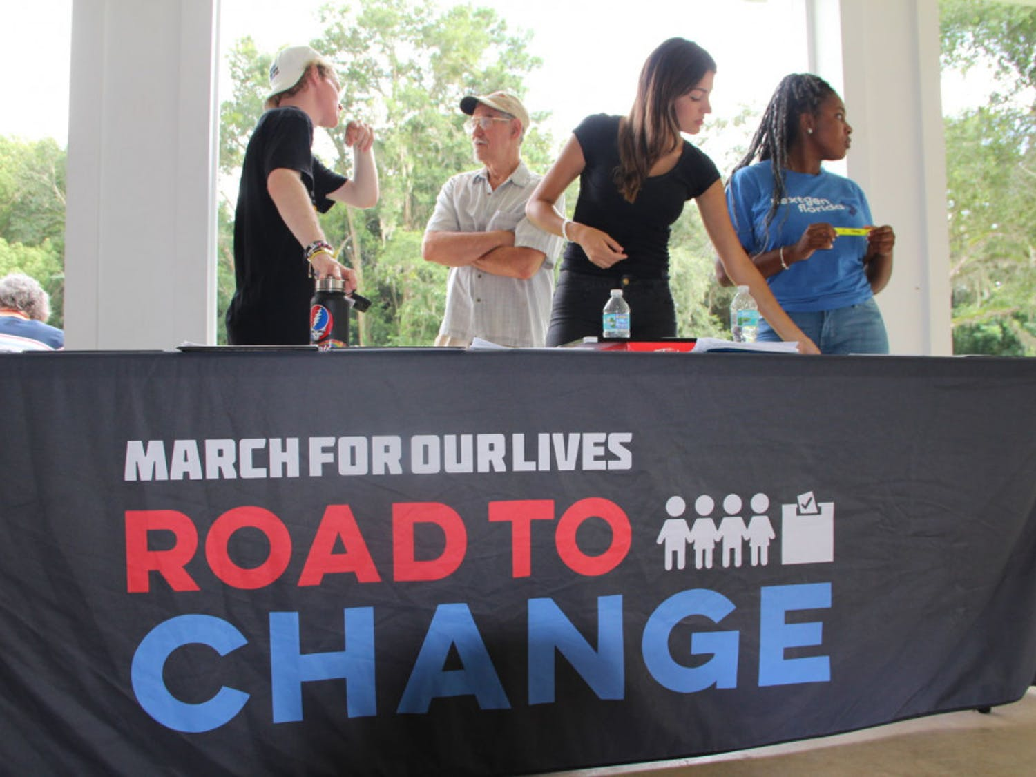 """Tom Bergan, David Finley, Ingrid Fernandes and Gracey Jean-Bernard stand behind a booth for """"March for our Lives — Road to Change."""""""