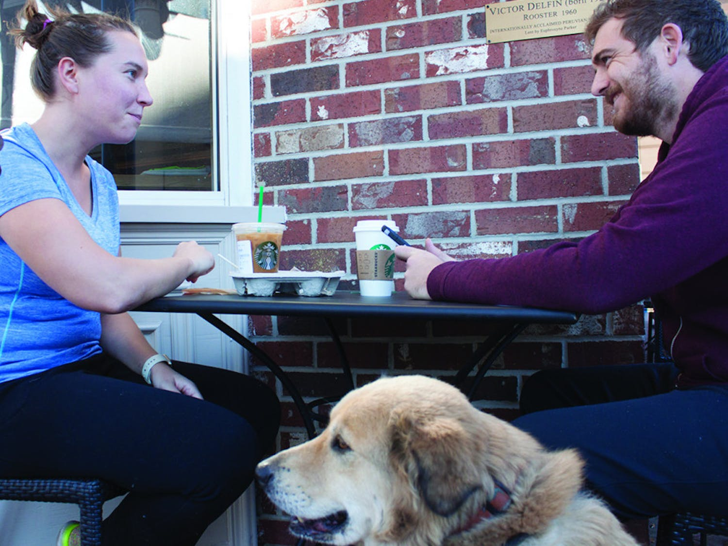 "Carolyn Witman, an anesthesia resident at UF, eats and drinks coffee with Ryan Butler and his dog, Penny, outside of the downtown Starbucks, located at 201 SE First St., on Monday. After the Starbucks CEO pledged to hire 10,000 refugees, #BoycottStarbucks started trending on Twitter. ""I'm anti-boycott and pro-Starbucks,"" Witman said."