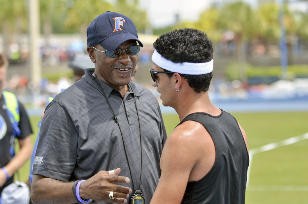 <p>UF track and field coach Mike Holloway talks with mid-distance runner Andres Arroyo on the final day of the 2015 Florida Relays on Saturday at the Percy Beard Track.</p>