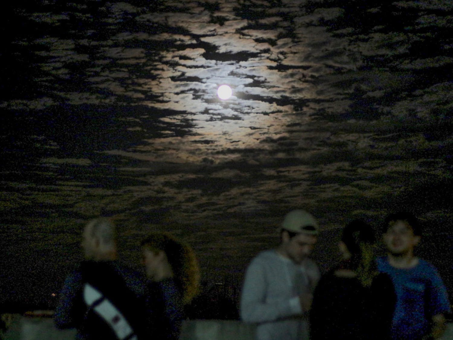 Gainesville residents and UF students watch the supermoon on the roof of a parking garage above Volta Coffee, Tea and Chocolate on Monday night. About 150 people showed up with dogs, roller blades and cameras to see the moon at its brightest and closest location to the Earth until the next supermoon in 2034.