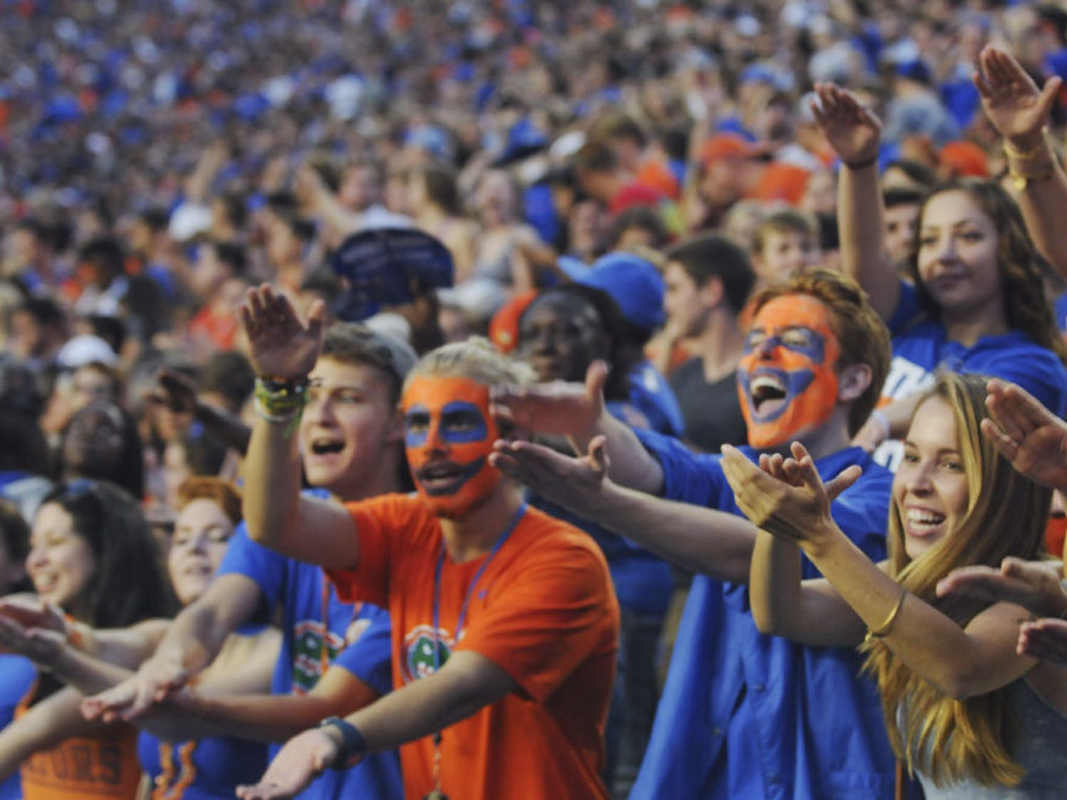 Faces painted in orange and blue, Erik Teriele (left), a UF mechanical engineer freshman, and Chris Crary, a UF computer engineer freshman, perform the Gator Chomp during the Gators' first game of the season. The 18-year-olds didn't expect to get the seats that they were assigned. Teriele said they were freaking out when they realized how close they would be to the field.