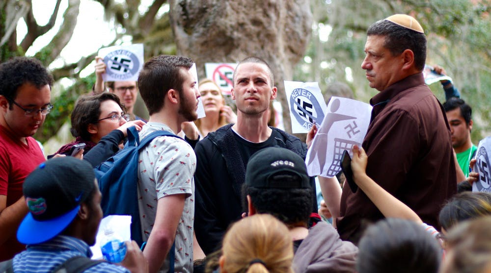 <p><span>Students protest and stand in front of the man wearing a swastika on Thursday.</span></p>