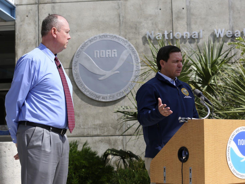 National Hurricane Center Director Ken Graham, left, looks on as Florida Gov. Ron DeSantis speaks about Tropical Storm Dorian outside of the the National Hurricane Center, Thursday, Aug. 29, 2019, in Miami. (AP Photo/Lynne Sladky)