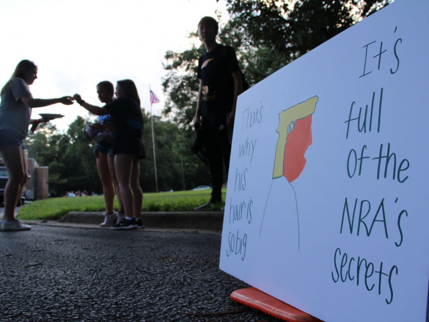 Madison Gore, an 18-year-old UF political science freshman, hangs with friends by her protest sign outside the Gainesville Woman's Club.