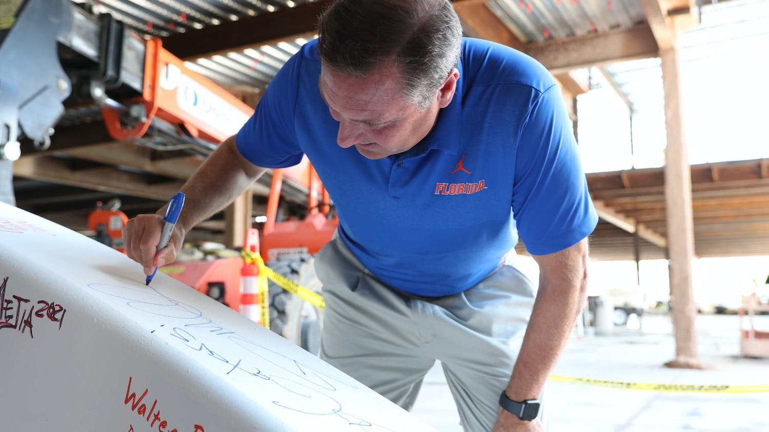 Dan Mullen signs a beam at Tuesday's ceremony for the new football center.