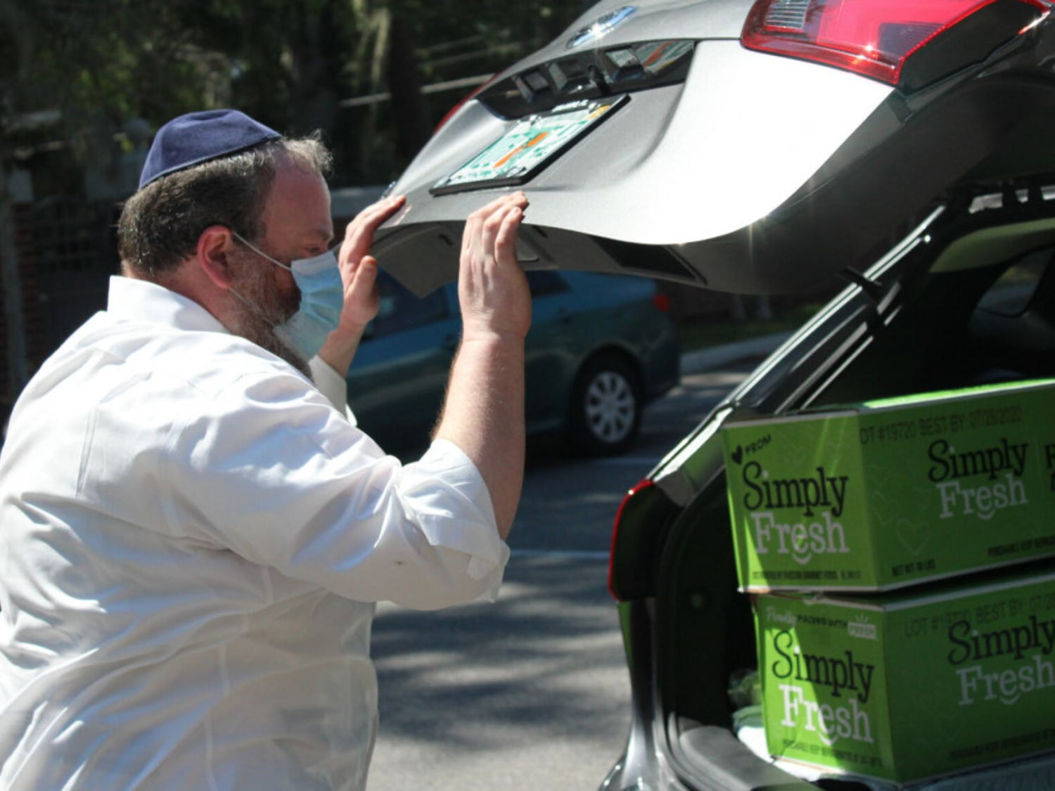 """Rabbi Berl Goldman helped load boxes of free fruits and vegetables into cars of community members. """"We need to share the spirit and energy of giving,"""" he said. """"People need help. Serving during happy times is exciting and positive but serving during a pandemic is what we are called to do. People need hope."""""""
