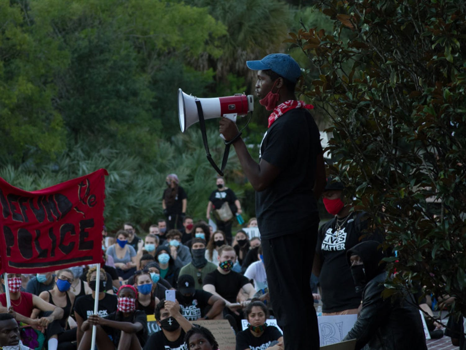 """At a June 13 demonstration near the Gainesville Police Department, protesters chant """"No justice, no peace,"""" and a sign reading """"Defund The Police"""" can be seen in the background."""