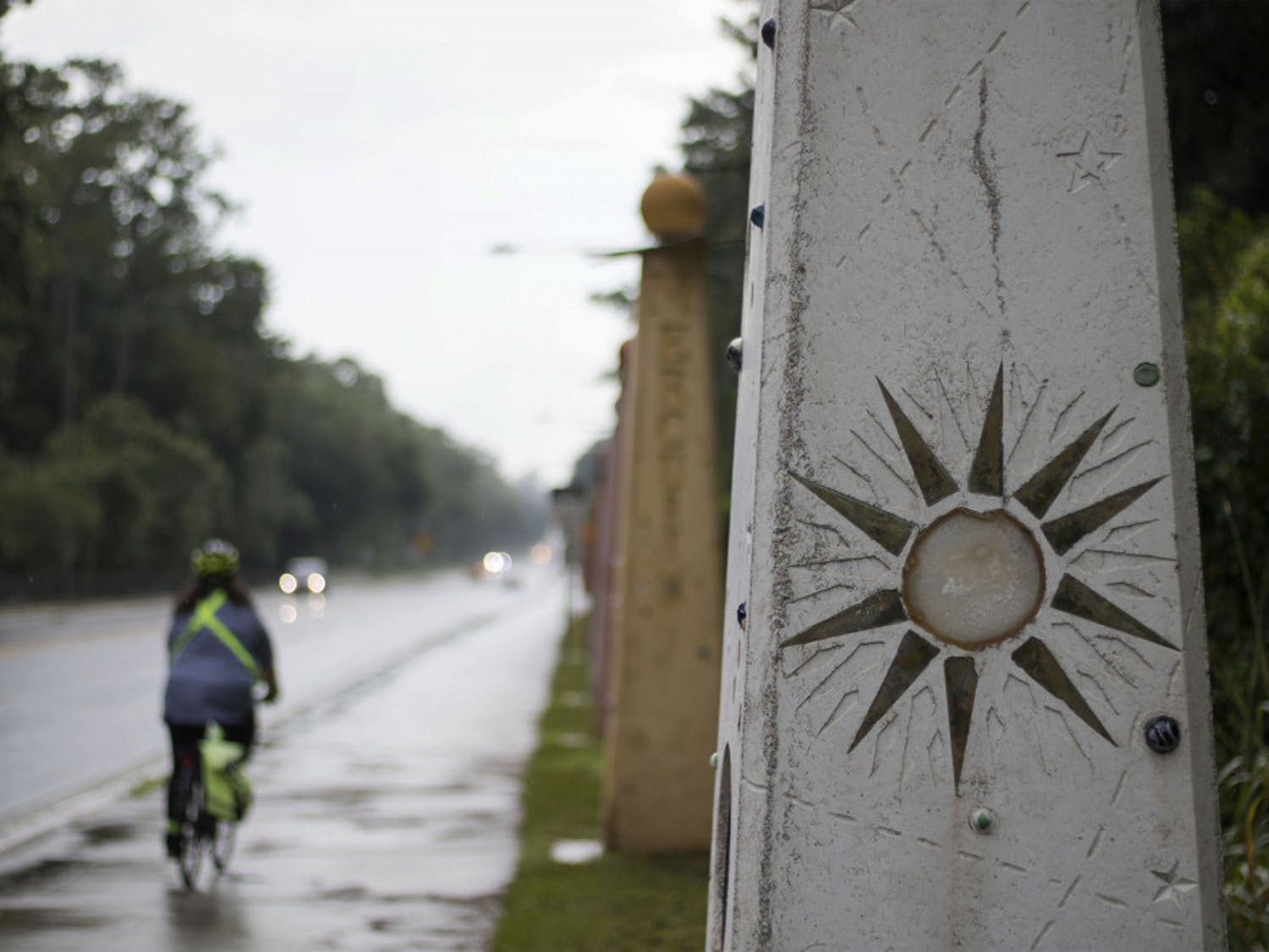 A biker passes by the statues Wednesday evening for Gainesville Solar Walk, a four billion to one scale model of the solar system located along NW 8th Avenue.