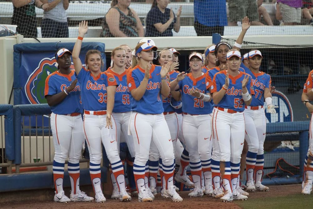 <p>The Gators applaud outside of their dugout during a game last season</p>