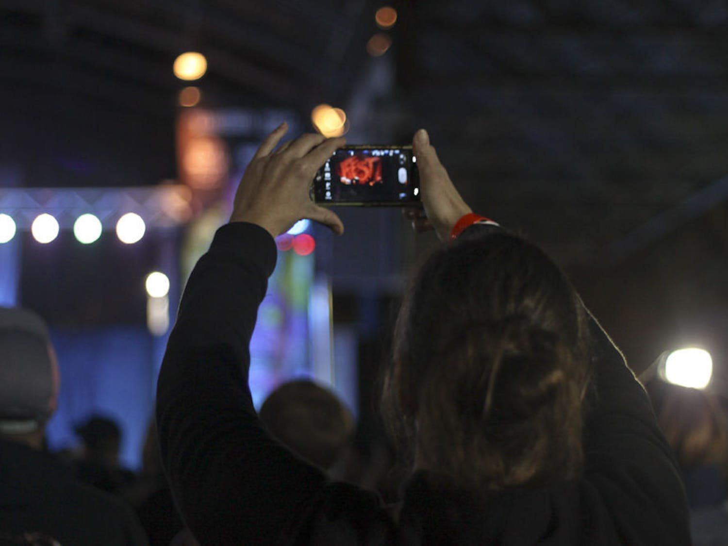 A fan takes a photo of Hot Water Music on Bo Diddley Community Plaza on Sunday night.