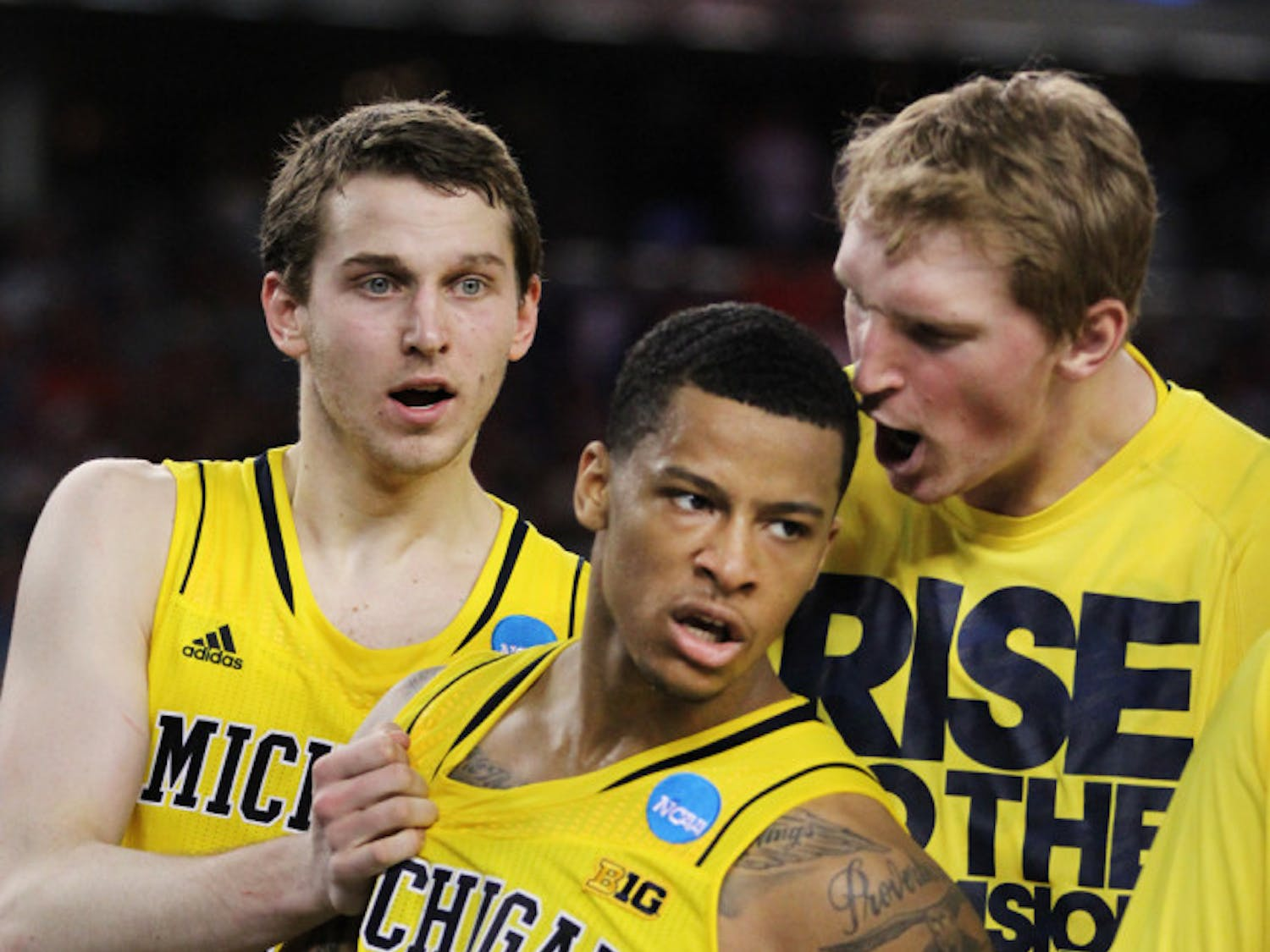 Guard Trey Burke (3) celebrates with his teammates during Michigan's 87-85 overtime win against Kansas on March 29 in Arlington, Texas.