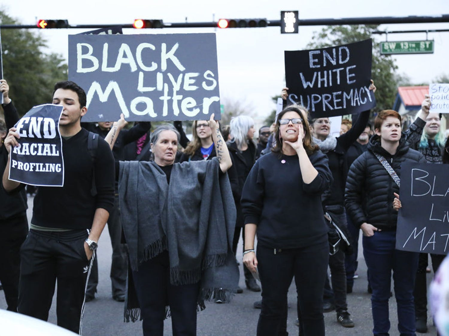 Protestors of the #BLACKLIVESMATTER march shout in unison as they block the intersection of 13th Street and University Ave on Monday afternoon.