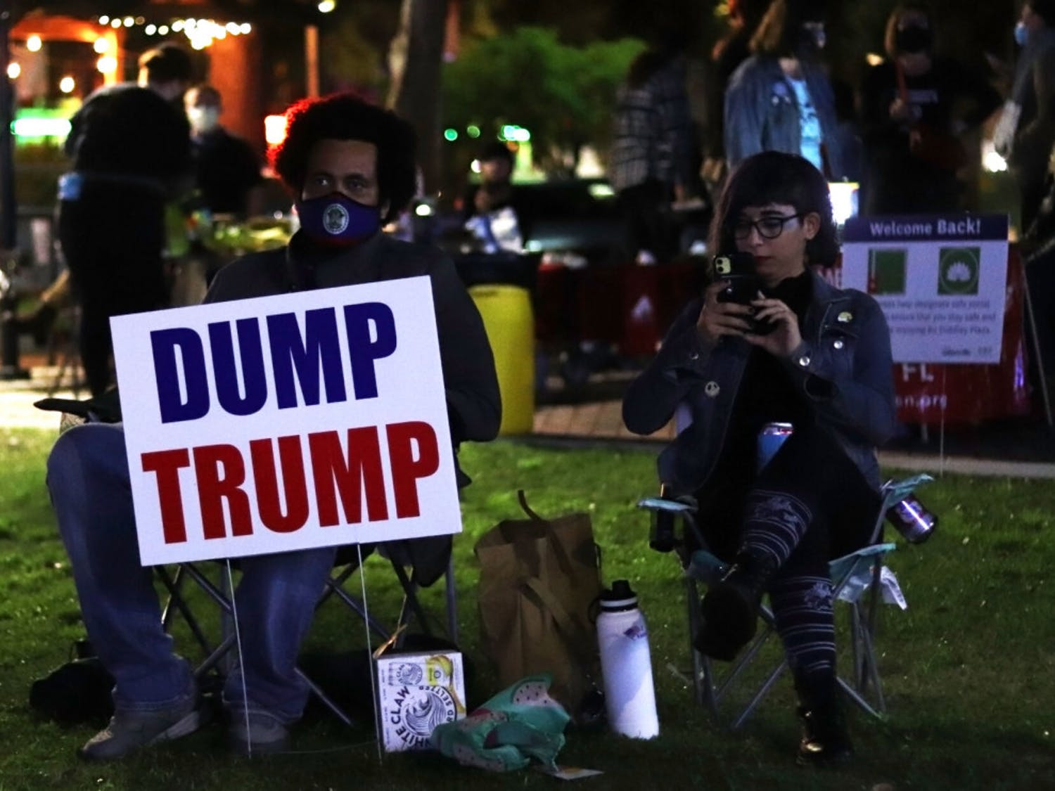 Justin McKenzie (left) and Dee Natour (right) sit in Bo Diddley Plaza during the election results watch party hosted by the Dream Defenders on Tuesday, Nov. 3, 2020. (Lauren Witte/Alligator Staff)