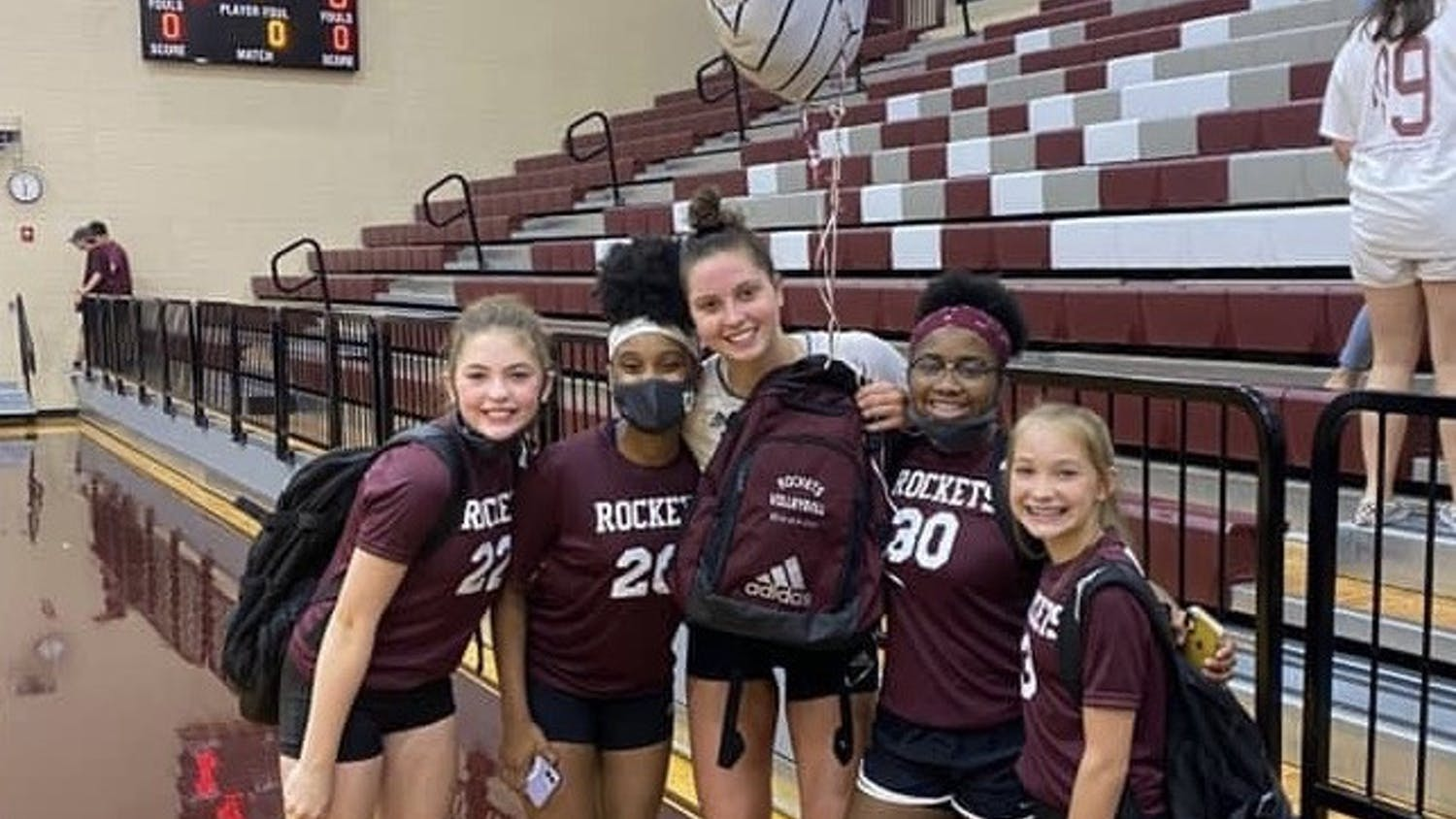 Florida's Merritt Beason (center), pictured while still in high school, poses with some of the middle school players she coached.