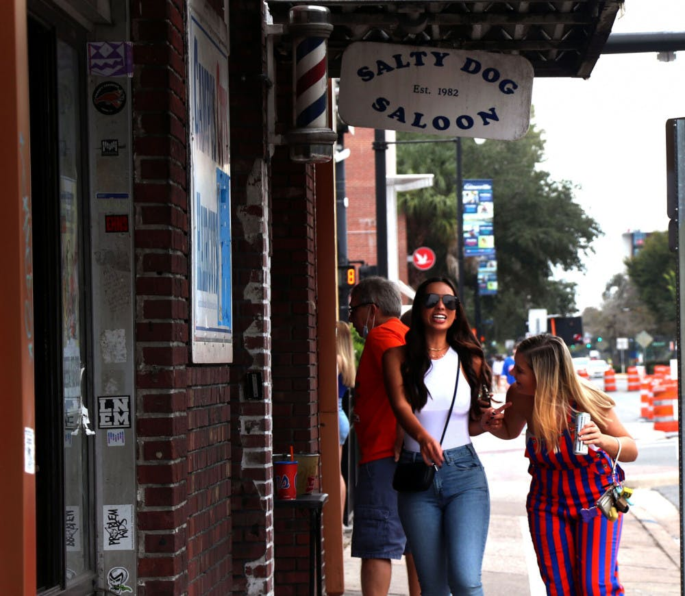 Photo of two women walking past Salty Dog Saloon