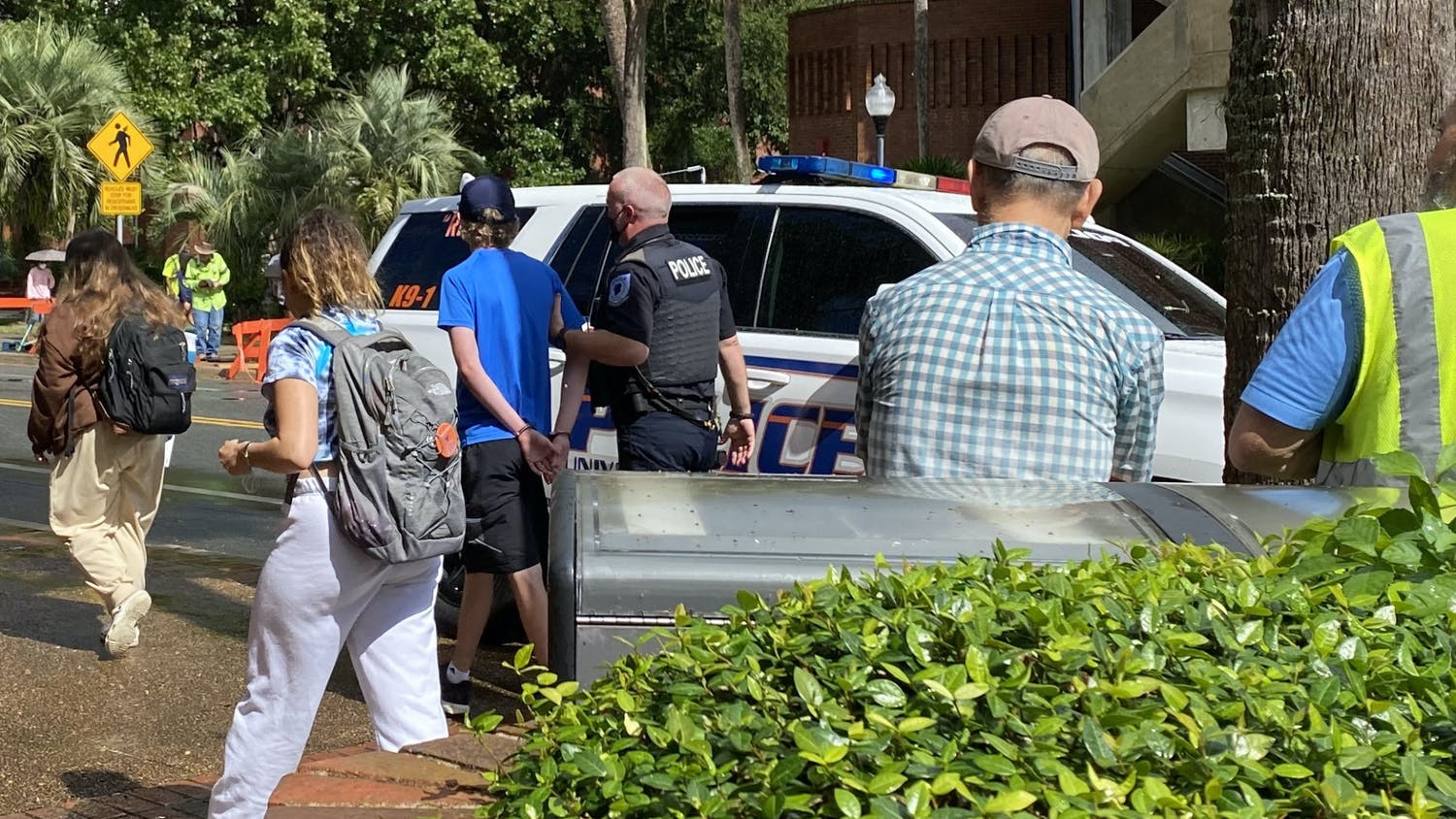 Joseph McDugald (middle), 18, UF freshman, is arrested by the University Police Department for refusing to leave an RTS bus in front of the Marston Science Library on Monday, Oct. 26, 2021. He was booked at the Alachua County Jail and released on Tuesday afternoon.