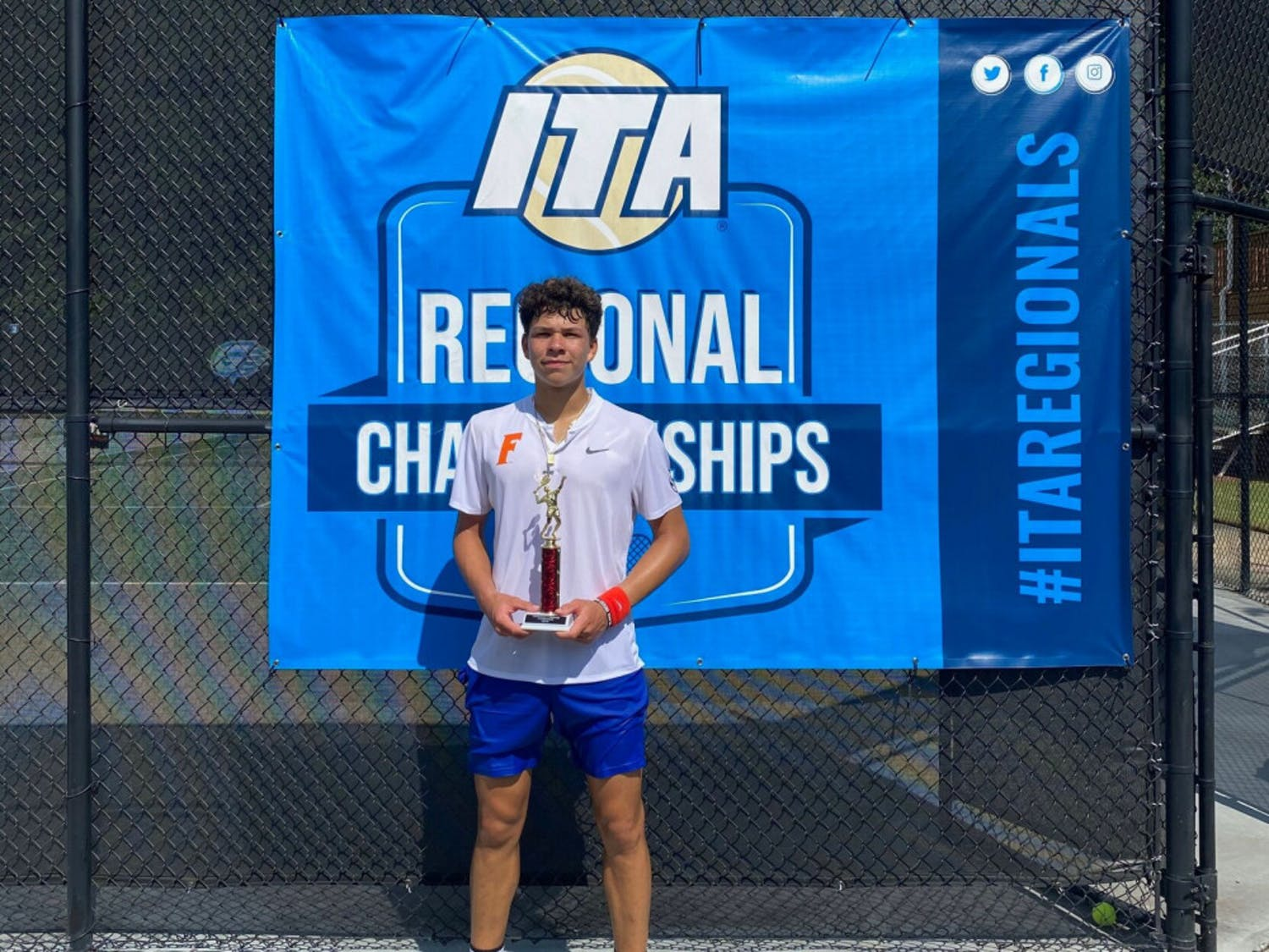 Freshman Ben Shelton stands with the trophy he earned after winning the ITA Fall CircuitPresented by Gwinnett Tennis.