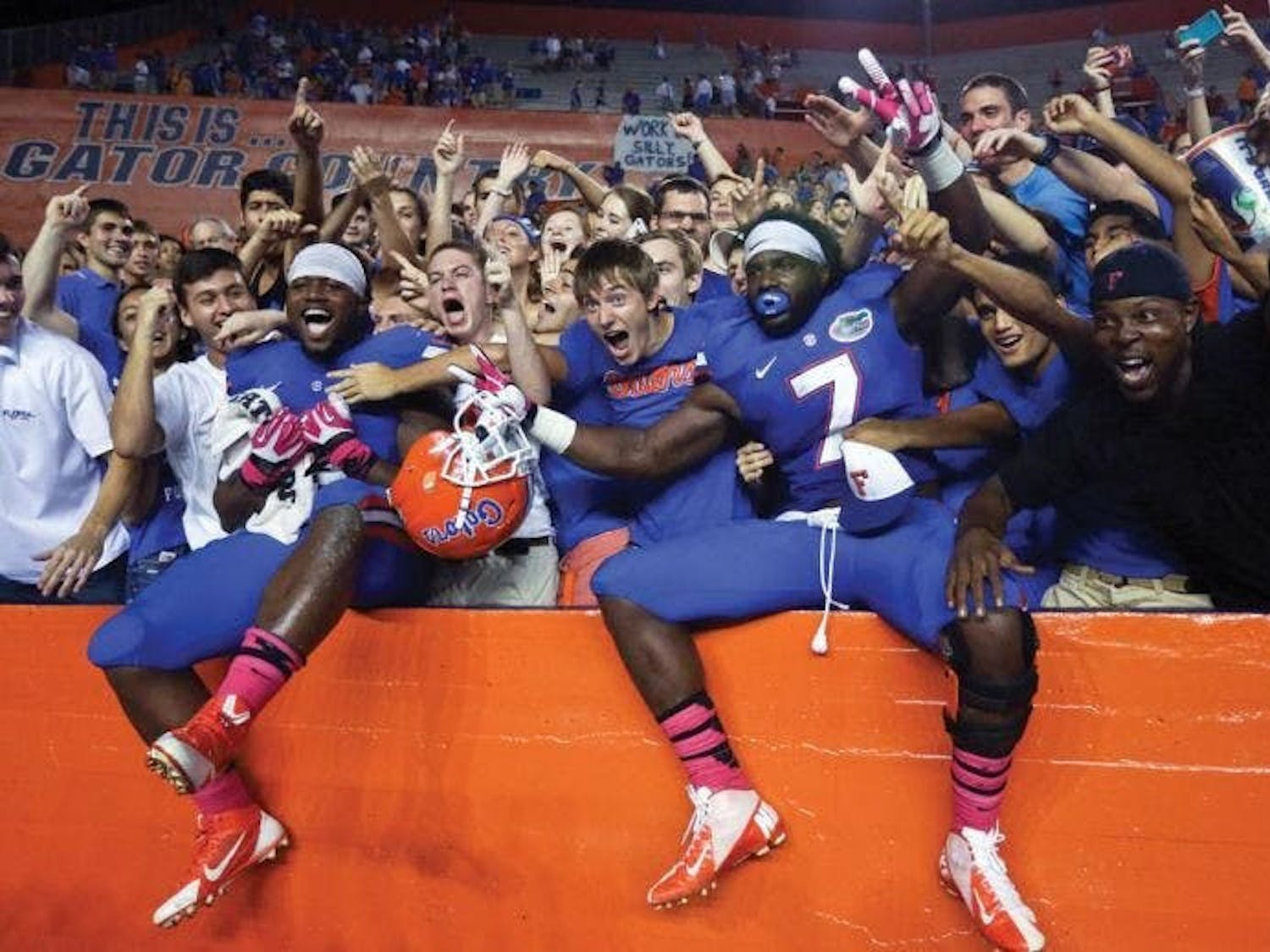 Florida football players celebrate with fans. The Swamp will see full attendance return in 2021