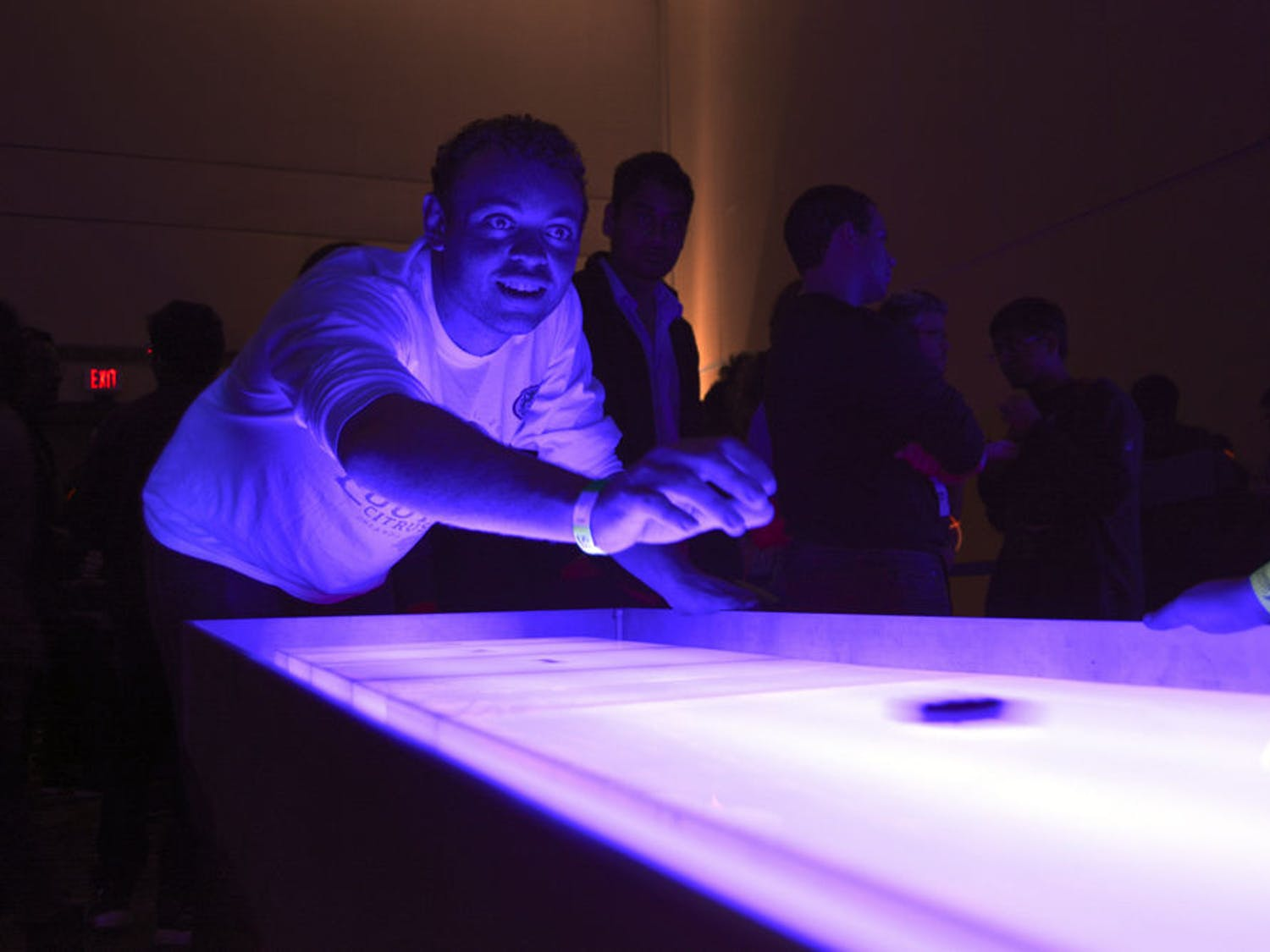 Zackery Bobb, a 19-year-old UF chemical engineering freshman, slides a disc across a glowing shuffleboard in the Reitz Union during GatorNights on January 8. Bobb said his friends convinced him to go.