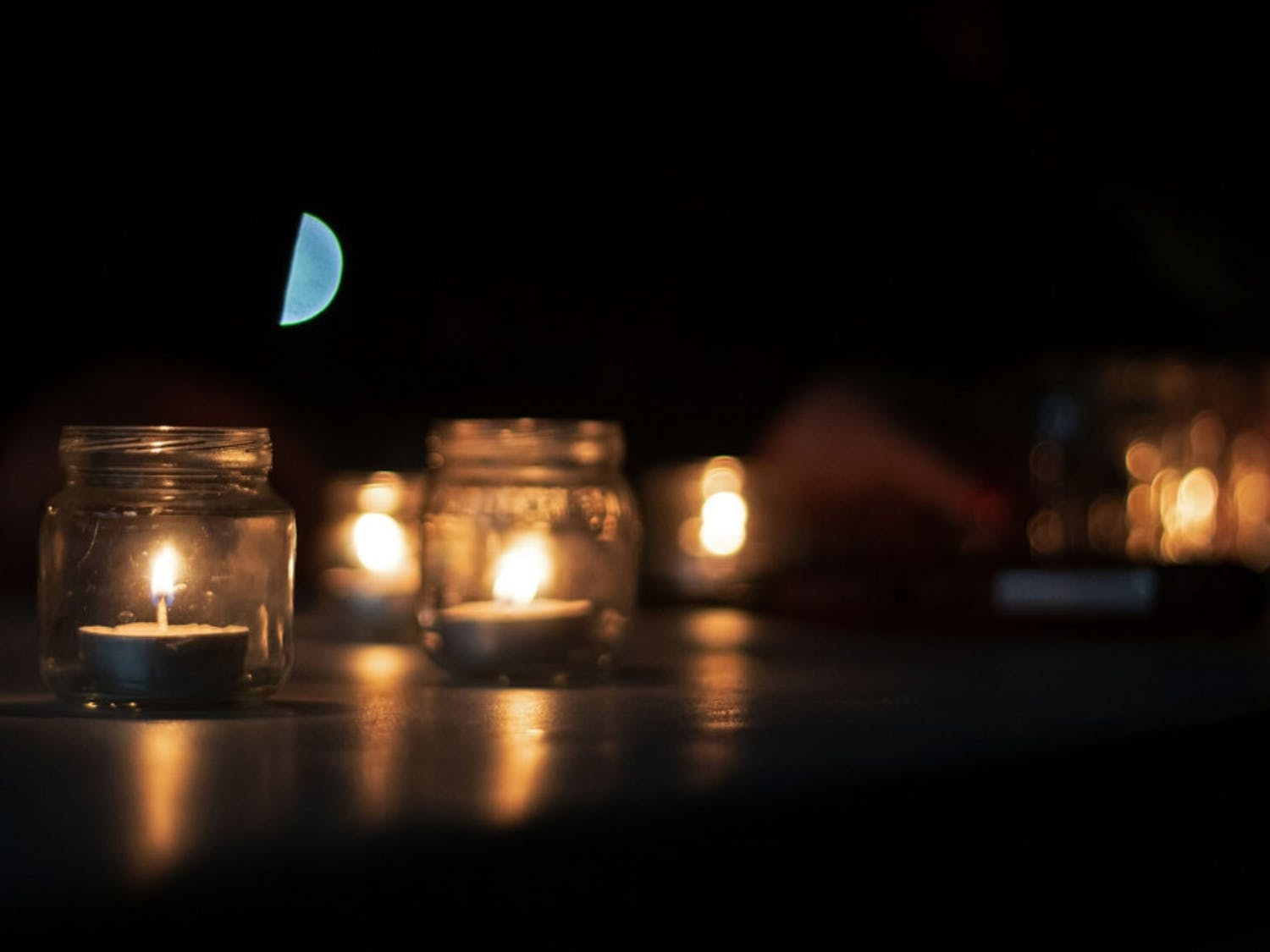 Volunteers light candles for the vigil during the Transgender Day of Remembrance at Depot Park Wednesday night.