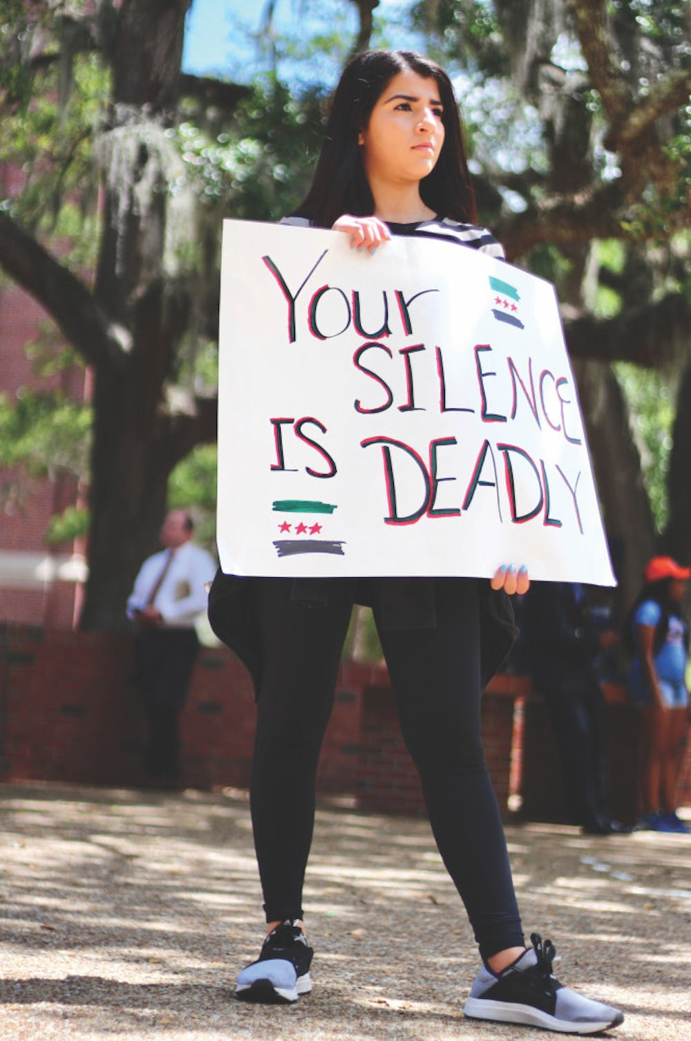 """<p dir=""""ltr""""><span>Rama Hussein, 21, a UF biology junior, holds a sign that reads """"Your Silence is Deadly"""" while members of Students Organize for Syria demonstrated a die-in.</span></p><p><span></span></p>"""