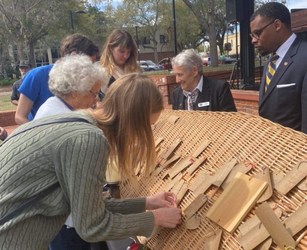 <p>Residents pictured are gathered around the lid of the coffin of Rose 'Granny' McDonald-Loston. They wrote notes to her and tied them onto the lid. She was buried after the service at Prairie Creek Conservation Cemetery, located at 7204 County Road 234.</p>