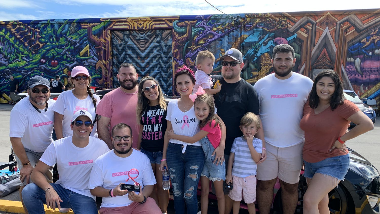 Michele Altomare (second from left) and Juan Reina (third from left), kneel on the ground as they pose with family and friends for a photograph during the third annual Breast Cancer Awareness Show in Tampa, Florida, where they raised awareness for cancer research on Sunday, October 13, 2019.