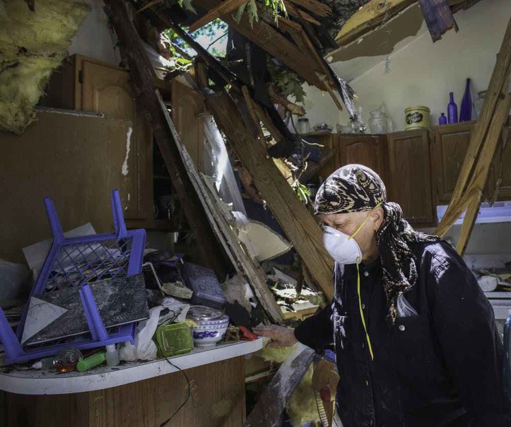 """<p class=""""p1"""">Alina Mitchell, 62, sorts through the debris in her kitchen after a tree crashed through the roof on Friday morning.</p>"""