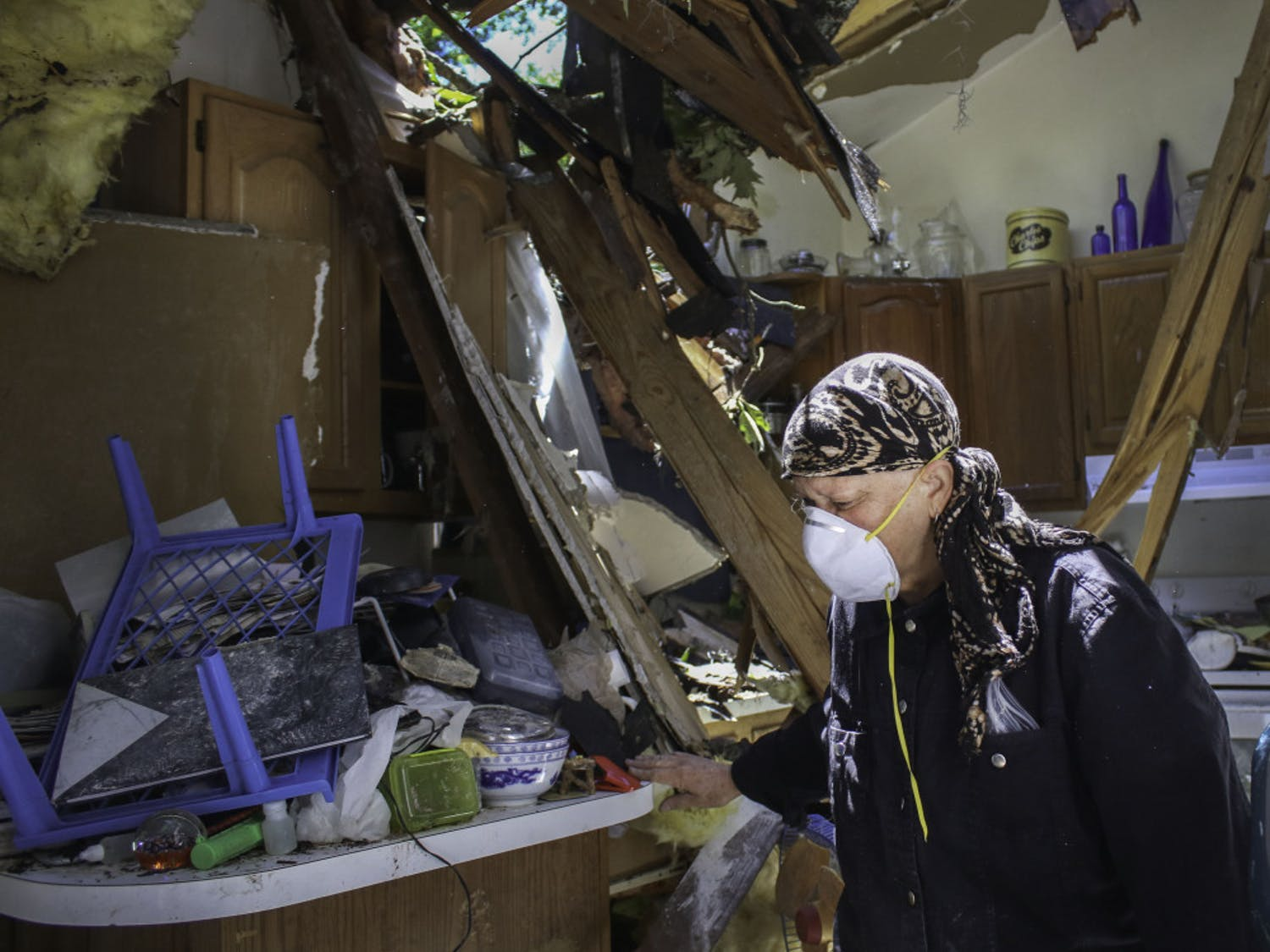 Alina Mitchell, 62, sorts through the debris in her kitchen after a tree crashed through the roof on Friday morning.