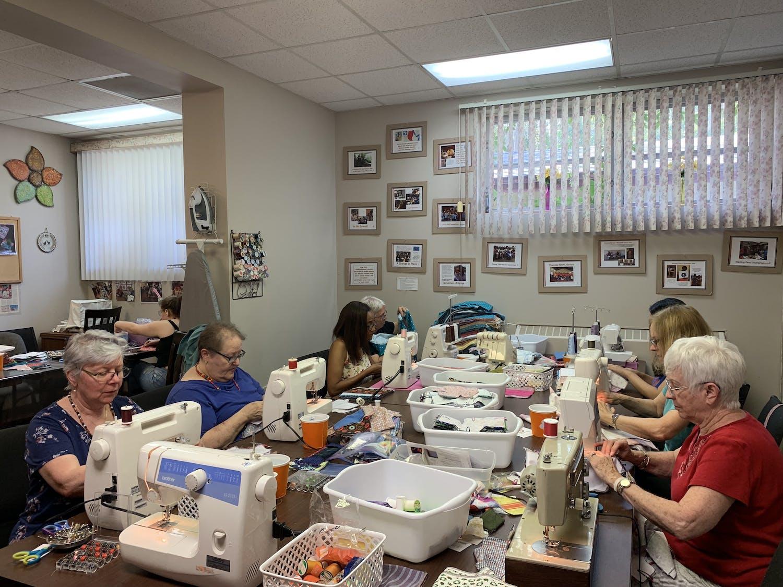 Volunteers work hard to sew reusable menstrual pads to help meet their goal of 200 kits.