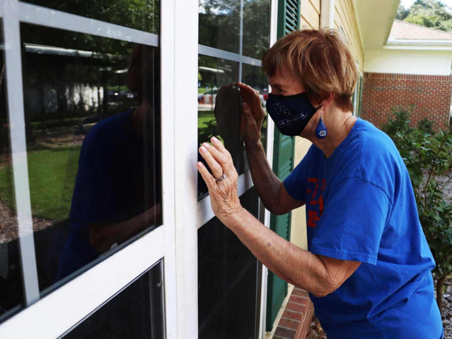Patsy Nelms waves to her husband, Warren Nelms, through his window in the assisted living building at Oak Hammock on Wednesday, Oct. 14, 2020. She cannot go inside.