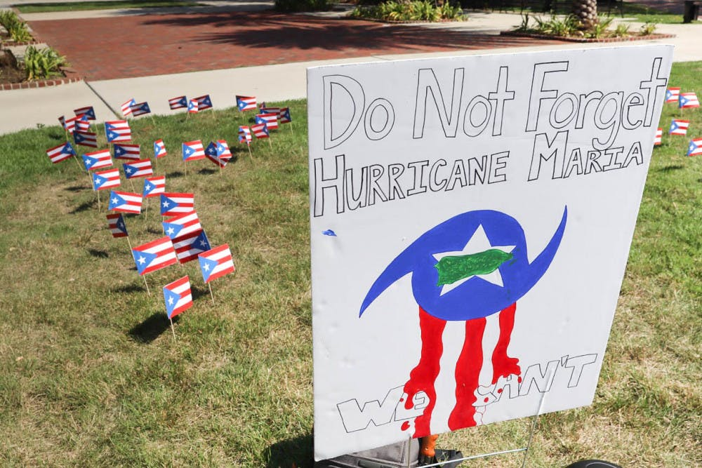 "<p><span id=""docs-internal-guid-dba3e83a-7fff-d4ed-707b-becf8a998d27""><span>Puerto Rican flags planted on the Plaza of the Americas in the shape of ""PR"" honored the victims of Hurricane Maria who died on the island on the anniversary of the hurricane.</span> <span>Unión de Estudiantes Puertorriqueños Activos, the Puerto Rican UF student group</span> <span>under the umbrella of Hispanic Student Association, collected books to send to a library and signed a poster offering words of hope to those still affected.</span></span></p>"