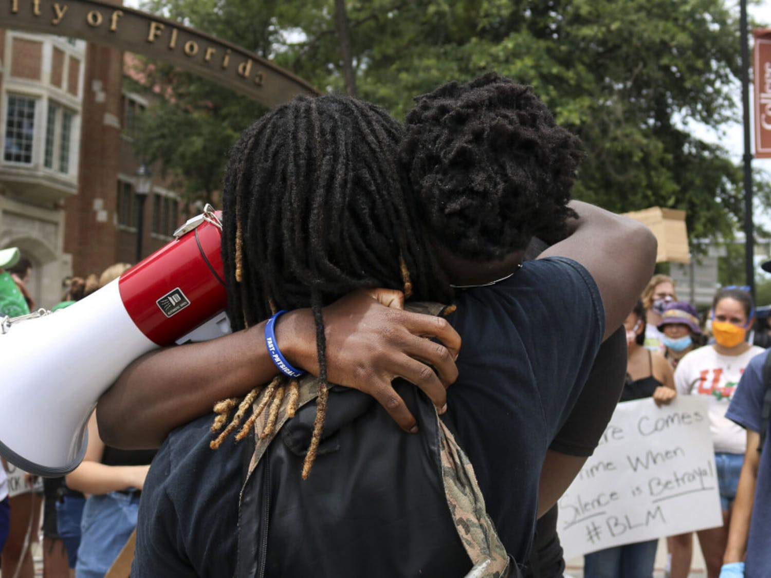 Morris McFadden, a 21-year-old telecommunications and production major and one of the organizers of the protest, hugs Clifford Taylor IV, a 21-year-old graphic design senior, Wednesday during a protest at the intersection of 13th Street and University Avenue against police brutality. The two hugged after Taylor spoke to the crowd.