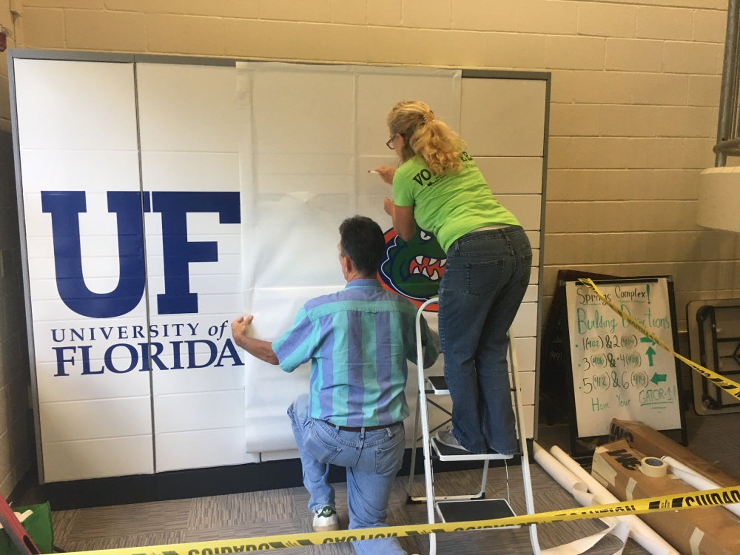 Jim and Starlyn Fikkert of Great Bay Signs install Gator decals to the mailing systems in Springs Complex. There is not an official operational start date for the lockers.