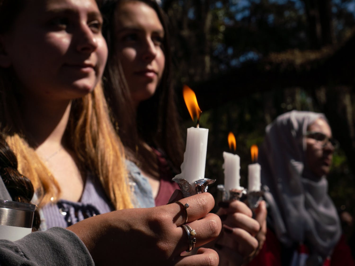 "UF student Ashley Cavallo (back left), 19, holds a candle to honor the lives lost in the Oct. 27 mass shooting at the Tree of Life Congregation in Pittsburgh, Pennsylvania. Cavallo, a UF biology sophomore with a minor in Jewish history, said, ""We will survive, we will continue on and we won't let terror stop us from...doing what we need to do."" The vigil was organized Monday by the Lubavitch Chabad Jewish Center, UF Hillel, the Jewish Student Union and was held at Turlington Plaza. Read the story here."