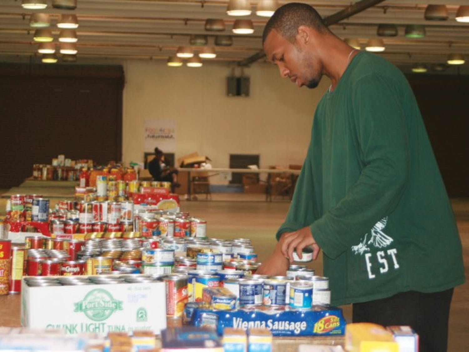 """Odori Hines, a 31-year-old UF alumnus, sorts food collected Monday during the Strike Out Hunger Food Drive at the Alachua County Fairgrounds. """"It's actually a lot of fun,"""" he said."""