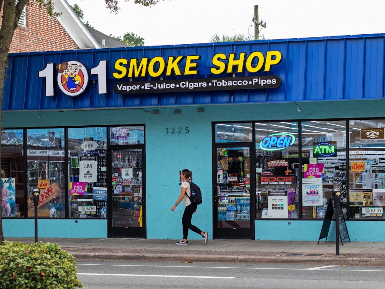 A woman walks by 101 Smoke Shop on SW Archer Road.