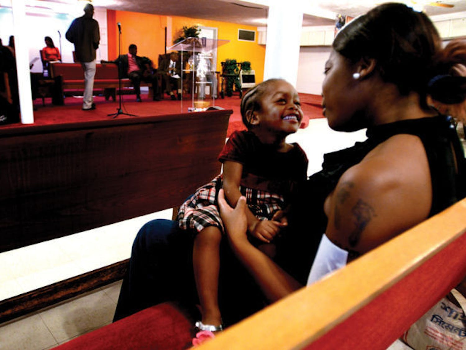 """Bessie Collins, 22, sits with her 2-year-old daughter Dayla Jones at the dedication service Sunday afternoon. """"I was surprised to see that the plaque was already up,"""" Collins said. """"I had no idea that this building was a part of history until Pastor Duncan told us."""""""