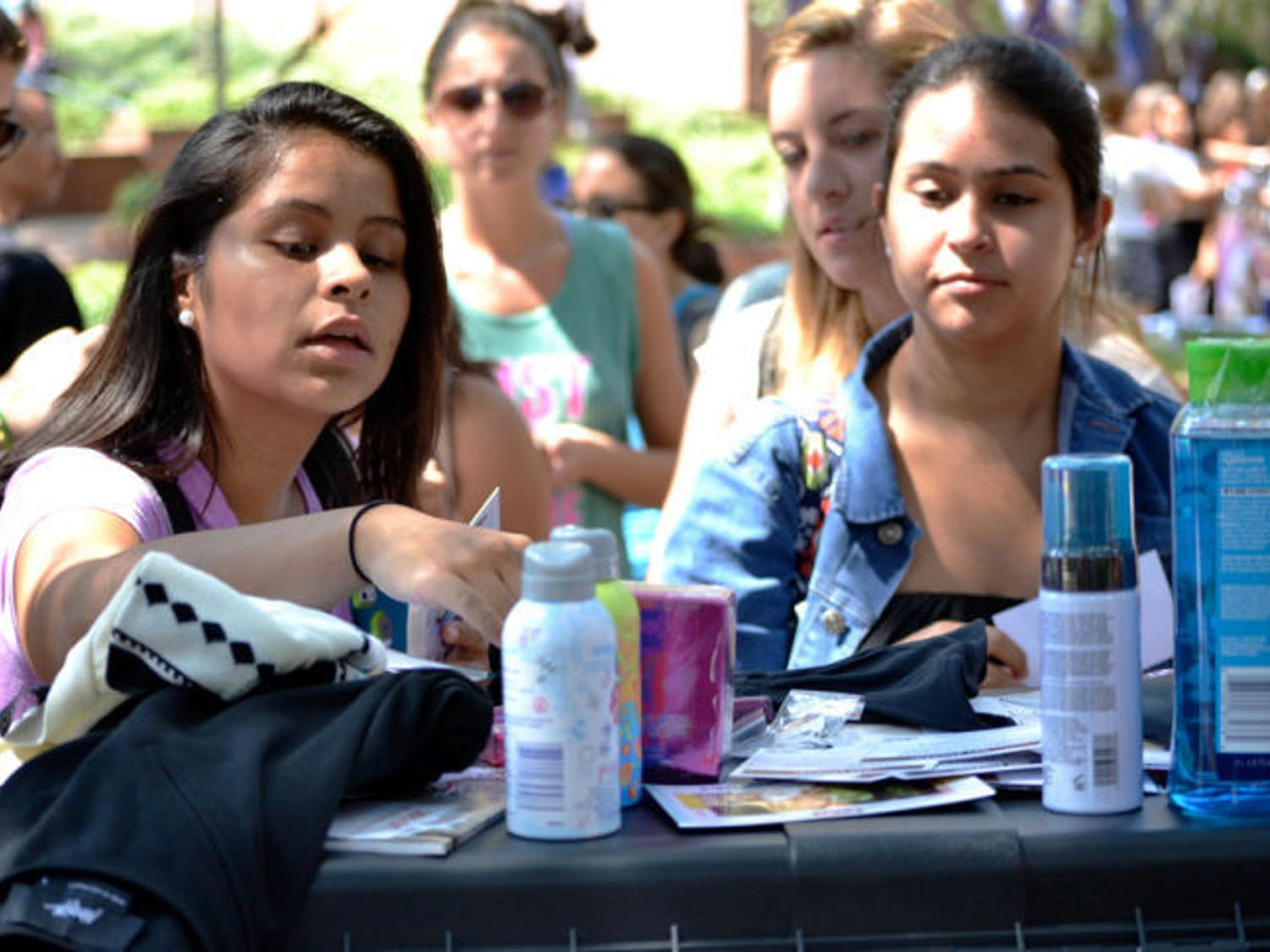 Michelle Tulande, left, reaches for items from a Teen Vogue giveaway event hosted by Her Campus Thursday on Turlington Plaza. The organization offered goodies to those who participated in social media challenges.