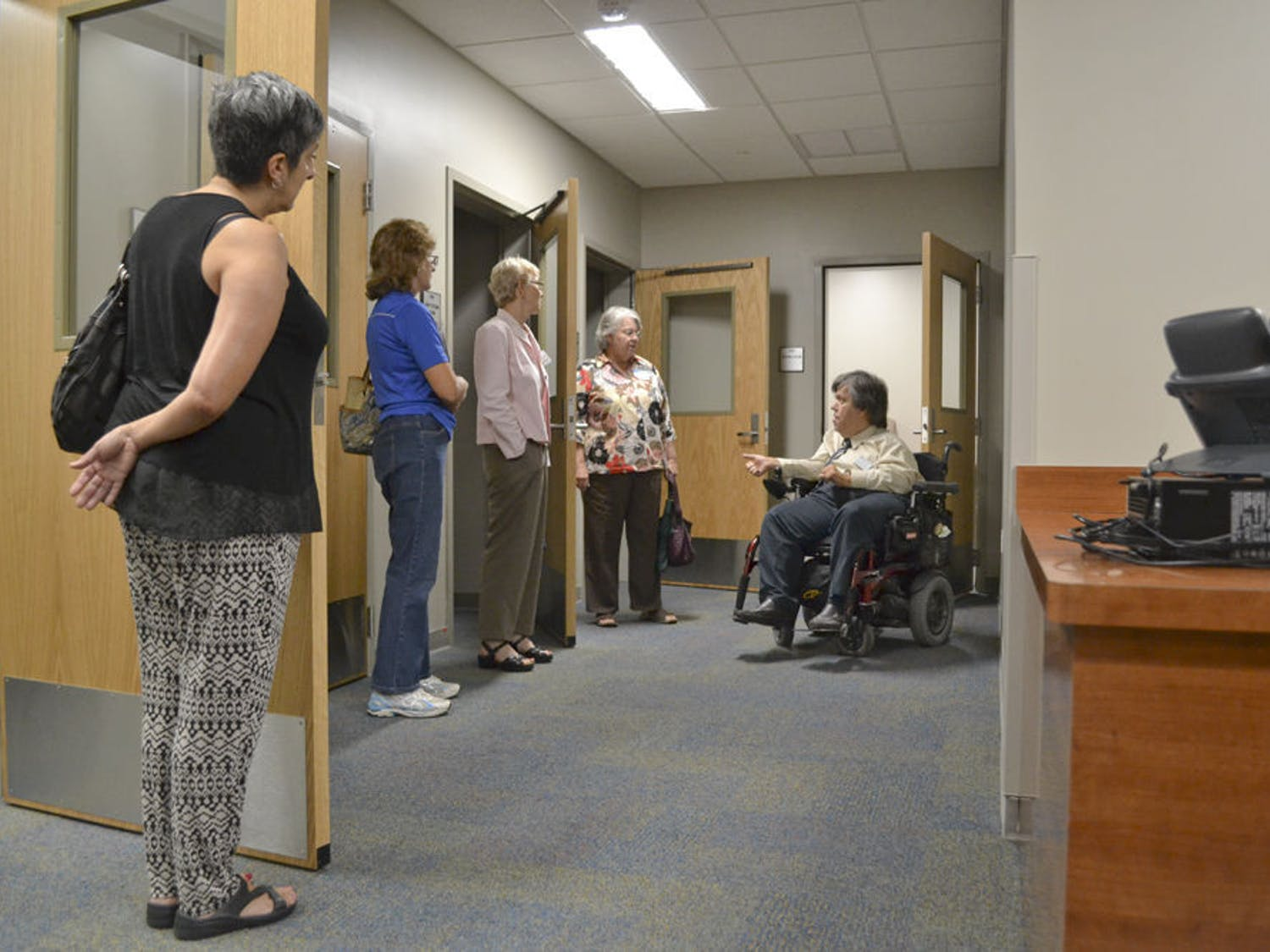 Rick Nelson (right), 57, advisor and educational training specialist at the Disability Resource Center, explains the functions of testing rooms to visitors during the DRC open house event at Cypress Hall Aug. 26, 2015.