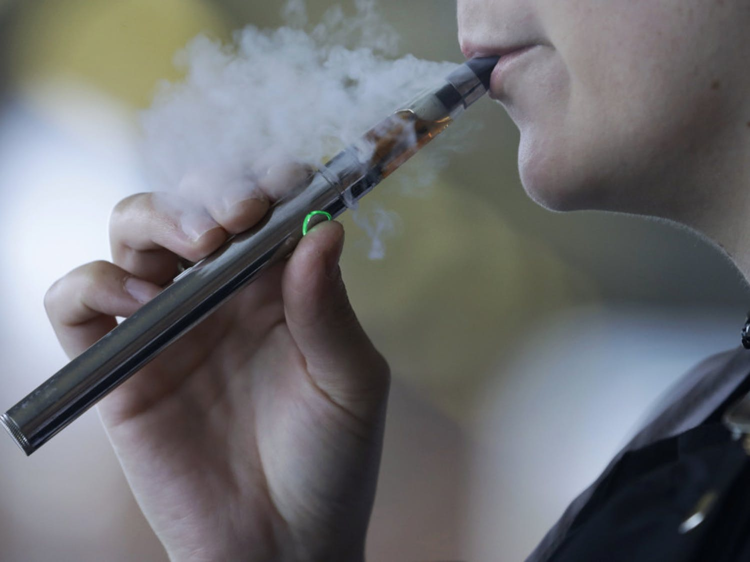 FILE - In this Friday, Oct. 4, 2019, file photo, a woman using an electronic cigarette exhales in Mayfield Heights, Ohio. A Michigan judge is blocking the state's two-week-old ban on flavored e-cigarettes. Court of Claims Judge Cynthia Stephens issued a preliminary injunction Tuesday, Oct. 15, 2019. She says Michigan Gov. Gretchen Whitmer's administration's delay in implementing the ban undercut its position that emergency rules were needed. (AP Photo/Tony Dejak, File)