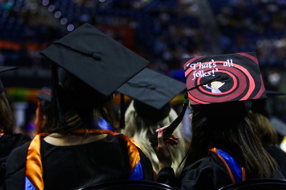 "<p>A Summer 2019 graduate of the University of Florida watches the remainder of the ceremony while wearing a graduation cap with the Porky Pig quote, ""That's all, folks,"" from Looney Tunes.</p>"