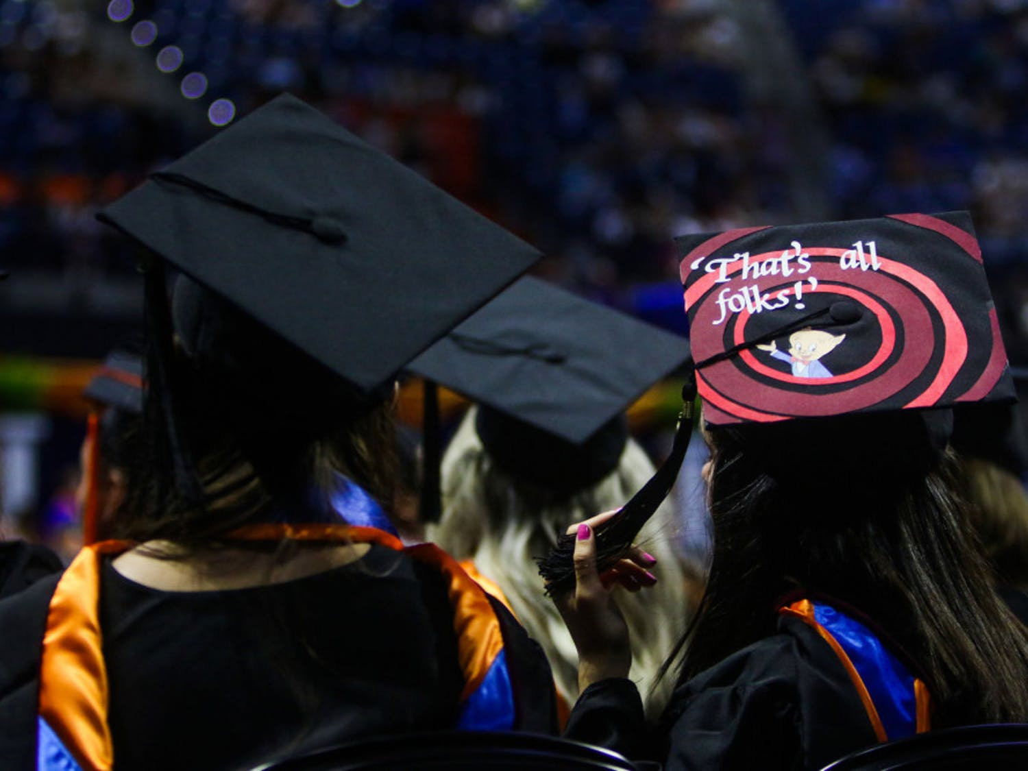 "A Summer 2019 graduate of the University of Florida watches the remainder of the ceremony while wearing a graduation cap with the Porky Pig quote, ""That's all, folks,"" from Looney Tunes."