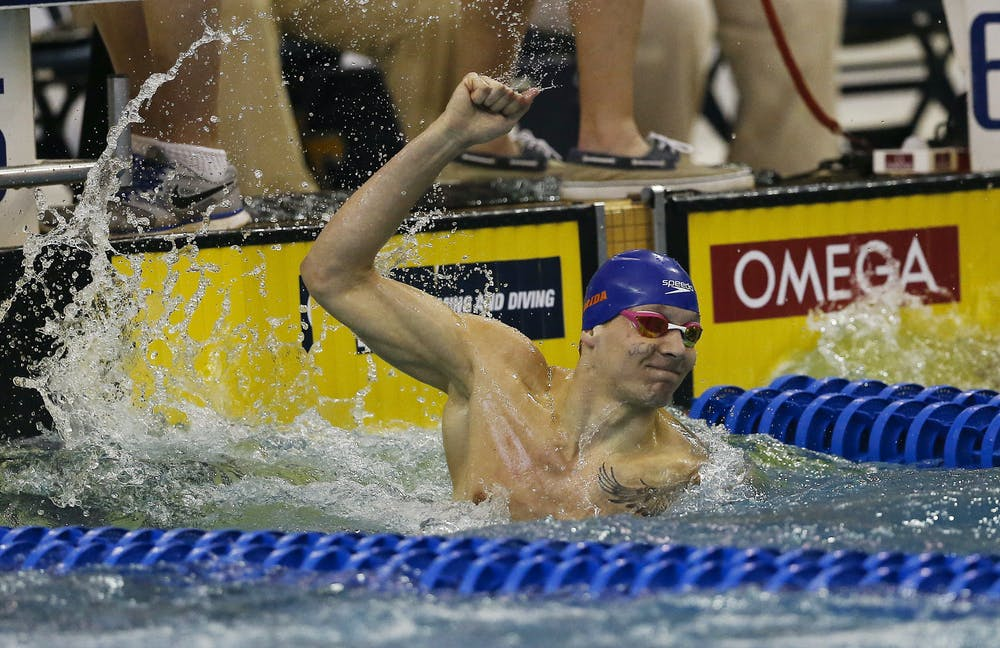 <p>Florida's Caeleb Dressel reacts after winning the 100-yard freestyle at the NCAA men's swimming and diving championships Saturday, March 26, 2016, in Atlanta. The initials on his face are in honor of a former teacher. (AP Photo/John Bazemore)</p>